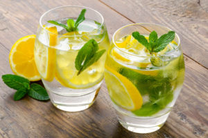 Preparation of the lemonade drink. Lemonade in two glass and lemon with mint on the table outdoor.